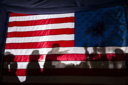 Barack Obama silhouetted behind a flag - Public Domain