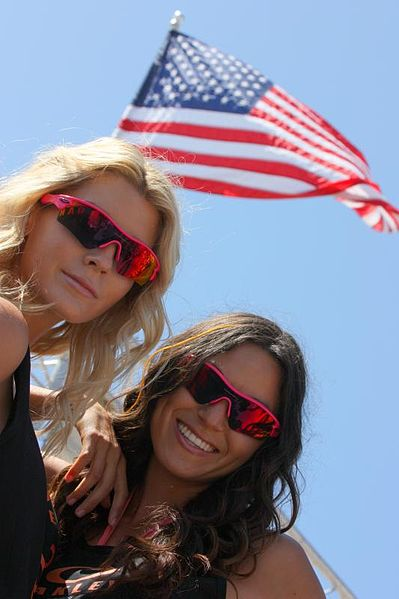 Women Wearing Oakley Sunglasses Under American Flag - Photo by Michael Dorausch